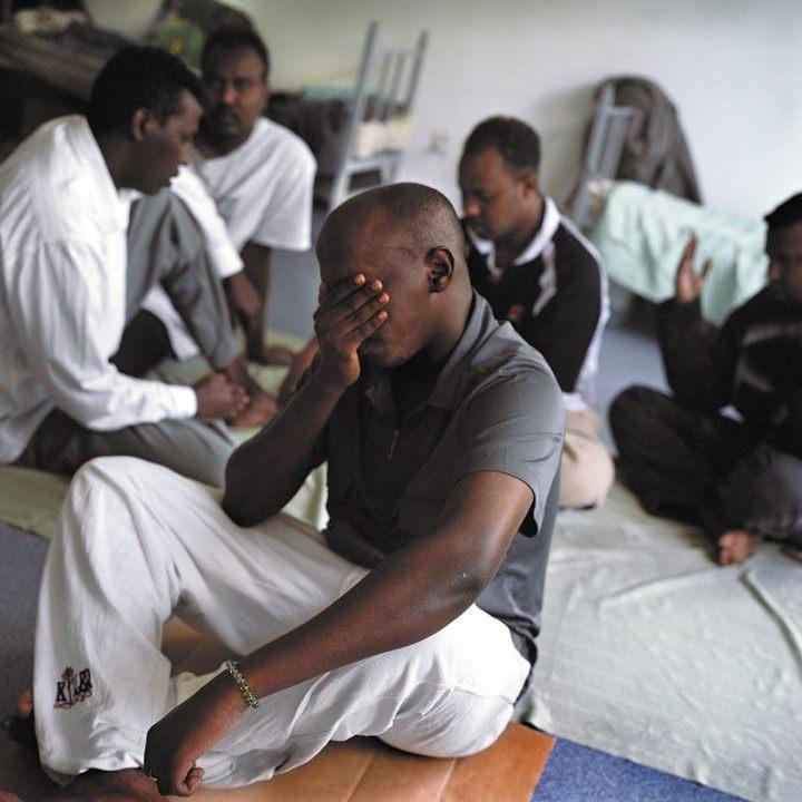 Sahal Yusuf Heyle (na pierwszym planie), od lewej - Abdullah Osman, Abdi Shire Jimcaale, Rooble Cali Qasim i Khadar Ahmad Faatax. Somalia. Ośrodek dla uchodźców w Lininie. Większość osób starających się o przyznanie statusu uchodźcy to praktykujący muzułmanie. W miarę możliwości modlitwę południową starają się prowadzić w grupie, pod przewodnictwem jednego z nich. Na zdjęciu chwila na refleksję indywidualną.